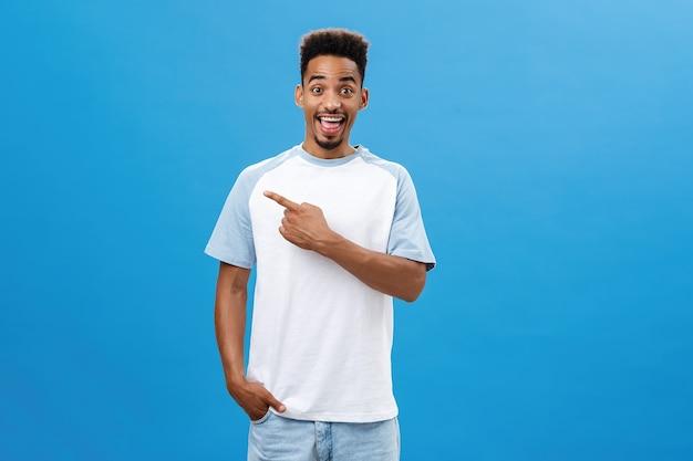 Begeisterter und bezauberter dunkelhäutiger kerl mit bart und afro-frisur, der fröhlich über blauem hintergrund steht und freudig auf die obere linke ecke zeigt, die hand in der tasche hält.