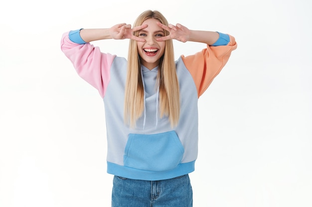 Begeistertes attraktives junges mädchen im hoodie, das friedenszeichen über den augen zeigt, lacht und lächelt
