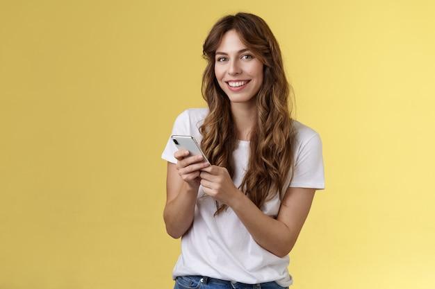 Begeistertes, gut aussehendes urbanes mädchen trägt weißes t-shirt, das lässig lächelnd erfreut kamera-sms hält smartphone-scroll-social-media-feed-ständer gelber hintergrund browsing-netzwerk