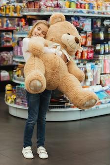 Begeistertes kleines mädchen, das großen teddybären hält
