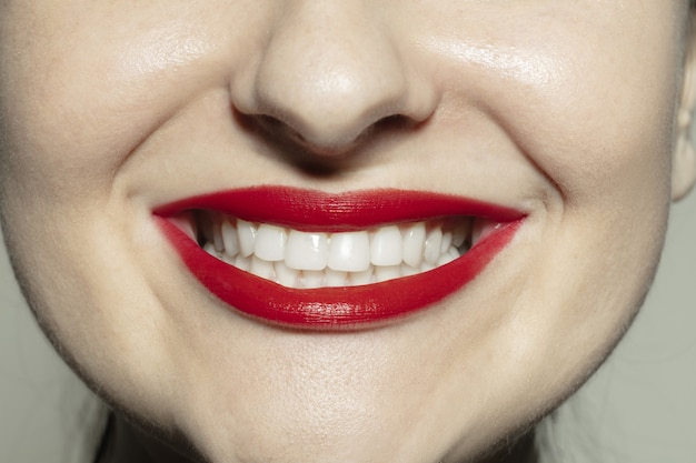 Begeistertes lächeln. nahaufnahme des weiblichen mundes mit leuchtend rotem glanzlippen-make-up und gepflegter wangenhaut.