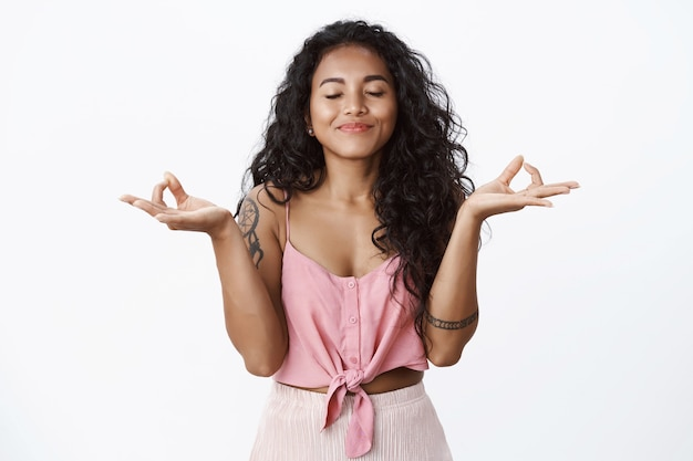 Begeistertes lockiges mädchen mit tattoos beim meditieren, hände heben in zen-geste, yoga praktizieren, augen schließen und glücklich lächeln, frische luft einatmen, erleichtert beruhigen, weiße wand