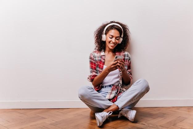 Begeistertes schwarzes mädchen, das mit gekreuzten beinen auf dem boden sitzt und musik genießt. nettes afrikanisches weibliches modell in kopfhörern, die telefonnachricht lesen.