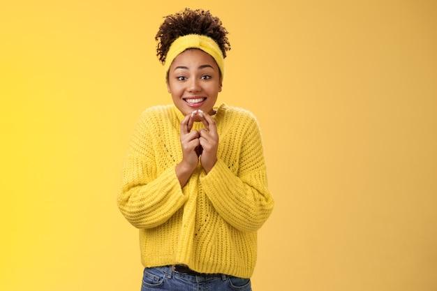 Begeistertes süßes, charmantes afroamerikanisches lächelndes mädchen, das die finger kreuzt, viel glück, die hände zusammendrücken, grinsend schauen, dass die kamera hoffentlich viel glück betet, der traum wahr wird, glaube, positive nachrichten zu erhalten.
