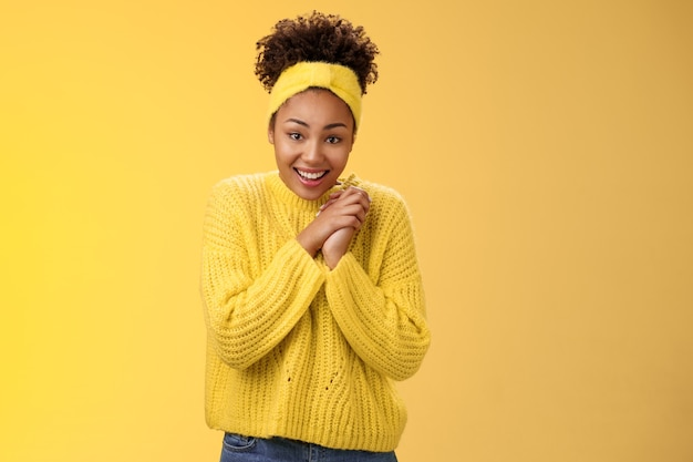 Begeistertes süßes charmantes afroamerikanisches lächelndes mädchen kreuzfinger viel glück hände zusammendrücken grinsend schauen hoffentlich kamera beten viel glück traum wird wahr glaube positive nachrichten erhalten