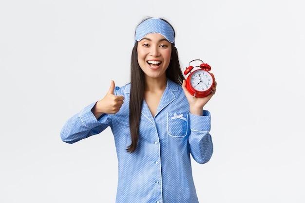 Begeistertes und glücklich lächelndes asiatisches mädchen in blauem pyjama und schlafmaske, das wecker und daumen hoch zur zustimmung zeigt, wie das frühe aufwachen für den morgenlauf, einen aktiven und gesunden lebensstil