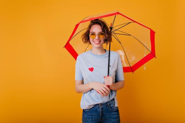 Begeistertes weibliches modell in der trendigen brille, die mit regenschirm steht und lächelt. studiofoto des lachenden lockigen europäischen mädchens mit sonnenschirm lokalisiert auf heller wand.
