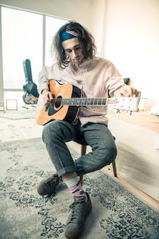 Beginn der persönlichen wiederholung. stilvoller, gut aussehender mann in hellem hemd, der vor dem täglichen üben ein musikinstrument aufstellt