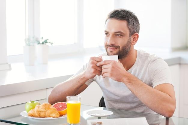 Beginnen sie den tag mit frischem und heißem kaffee. hübscher junger mann, der frischen kaffee genießt, während er in der küche sitzt