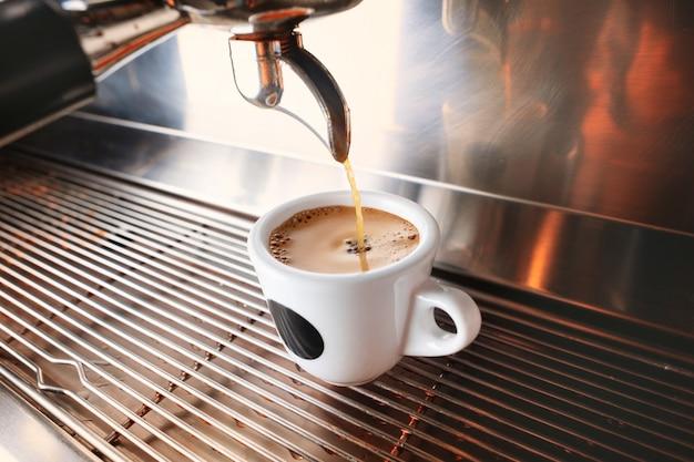 Beginnen sie ihren tag mit einer tasse aromatischem getränk. stilvolle schwarze espressomaschine, die kaffee brüht, im café geschossen.