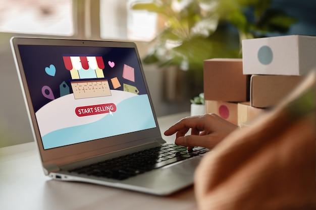 Beginnen sie mit dem verkauf von online-konzepten. junge frau, die computer-laptop benutzt, um ihren eigenen laden im online-marktplatz zu eröffnen. internet, das menschen hilft, von zu hause aus zu arbeiten