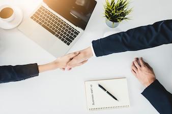 Beginnen Sie oben Geschäftsleute, die Hände mit Investor schütteln, bevor Sie verhandeln und planen