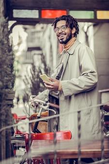 Begleite mich. erfreute männliche person, die ein lächeln auf seinem gesicht hält, während sie in der straße geht