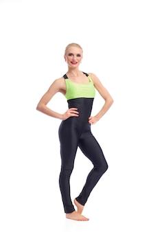 Begleite mich ins fitnessstudio. ganzaufnahme einer schönen sportlerin, die in die kamera lächelt und selbstbewusst auf weißem fitnesstrainer posiert