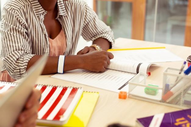 Begleiten sie uns. nahaufnahme einer internationalen frau, die ihr arbeitsbuch öffnet, während sie eine grammatikübung abschließt