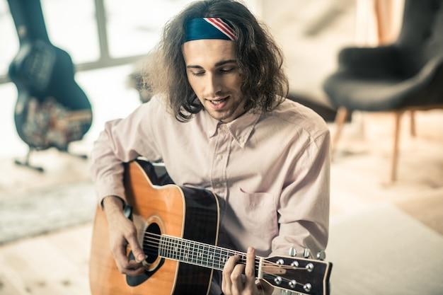 Begleitung mit gitarre. gut aussehender junger sänger in hellem bandana, der ein musikalisches hobby hat und viel zeit mit gitarre verbringt