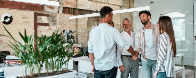 Begrüßen sie zwei männer, die sich die hände schütteln und lächeln, während sie mit kollegen im kreativbüro stehen