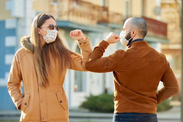 Begrüßung des ellenbogens, um die ausbreitung des coronavirus (covid-19) zu vermeiden. ein mann und eine frau in medizinischen gesichtsmasken treffen sich mit bloßen händen auf der straße. anstatt mit einer umarmung oder einem händedruck zu grüßen, stoßen sie an die ellbogen.