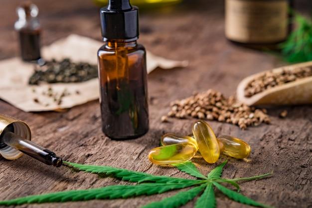 Behälter mit ätherischem cannabisöl mit cannabisblättern und hanfsamen