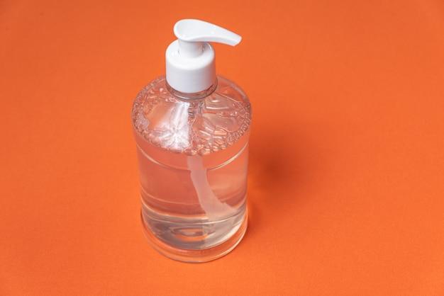 Behälter mit alkoholgel an der orangefarbenen wand