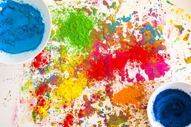 Behälter mit blauen farben in der nähe von haufen von hellen, trockenen farben