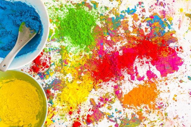 Behälter mit blauen und gelben farben nahe stapel von hellen trockenen farben