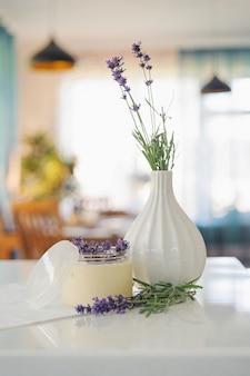 Behälter mit creme für den körper und lavendeldekoration auf weißer tabelle.