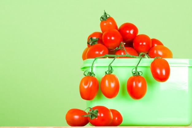 Behälter mit frischen tomaten auf grünem hintergrund