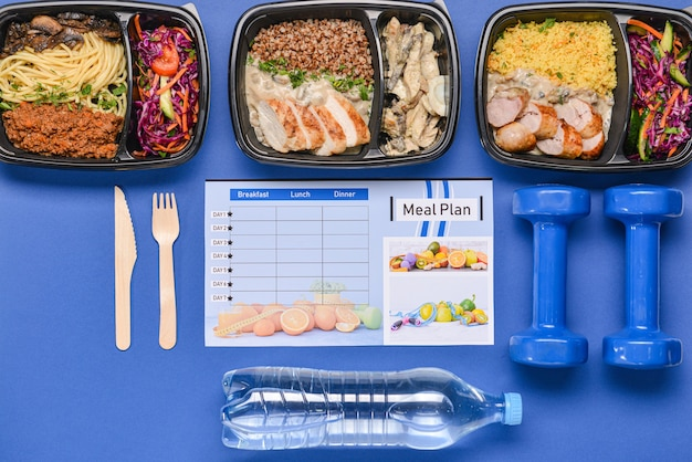 Behälter mit gesundem essen, flasche wasser, hanteln und speiseplan auf farbe