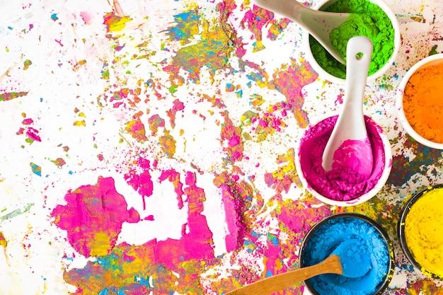 Behälter mit löffeln und hellen trockenen farben