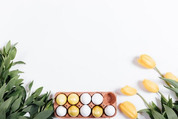 Behälter mit ostereiern und gelben tulpen auf einem weißen hintergrund, raum für text