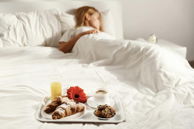 Behälter mit tasse kaffee, glas saft, roter blume, hörnchen und plätzchen steht auf weißem bett, während frau schläft