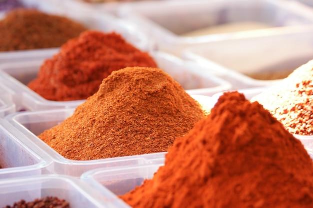 Behälter mit verschiedenen orientalischen gewürzen. verschiedene pulvergewürze in plastikboxen. türkischer gewürzladen. traditionelle orientalische küche.