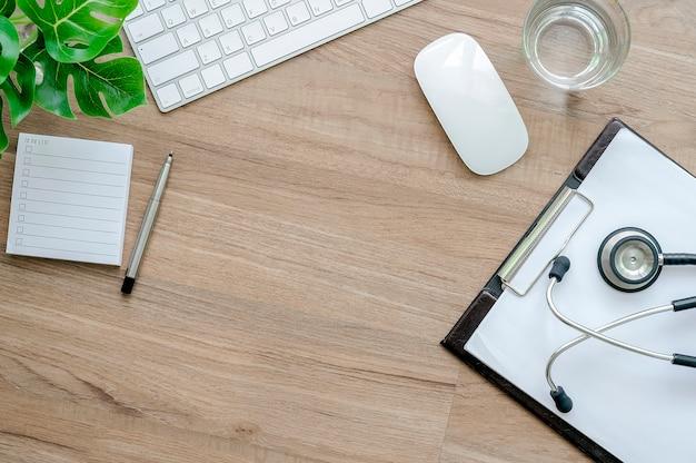 Behandeln sie arbeitsschreibtischkonzept, weiße tastatur, maus, diagramm und stethoskop auf holztisch.
