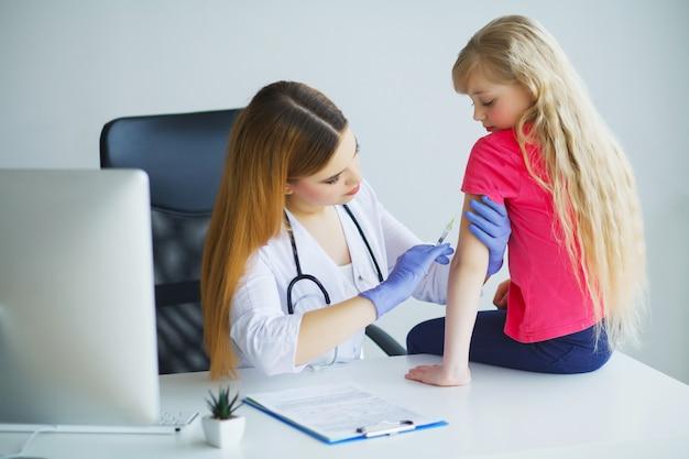 Behandeln sie das einspritzen der schutzimpfung im mädchen des kleinen kindes des armes, im gesunden und medizinischen konzept