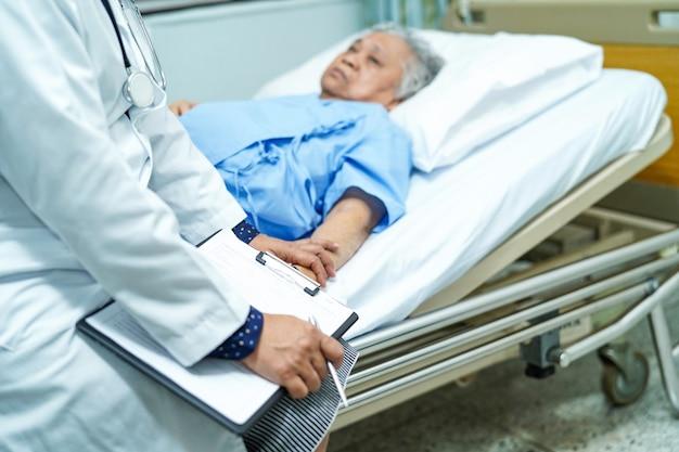 Behandeln sie das sprechen über diagnose und anmerkung über klemmbrett mit asiatischem senior