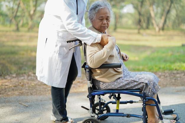 Behandeln sie den asiatischen älteren frauenpatienten der hilfe und der sorgfalt, der auf rollstuhl im park sitzt.