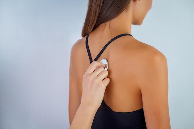 Behandeln sie die prüfung der atmung mit stethoscop eines weiblichen patienten.