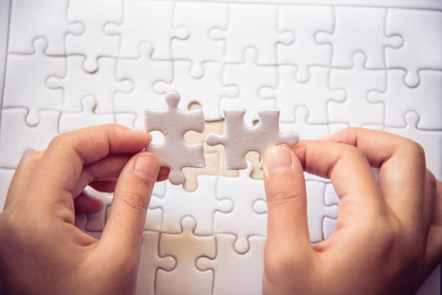 Behandeln sie ein stück weiße puzzles, die fallen sollen, um ein vollständiges arbeitsblatt zu erhalten