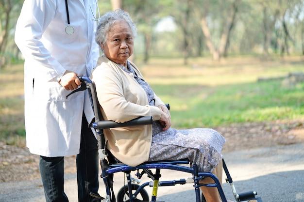 Behandeln sie hilfe und sorgfalt asiatischen älteren frauenpatient der alten dame, der auf rollstuhl am park sitzt.