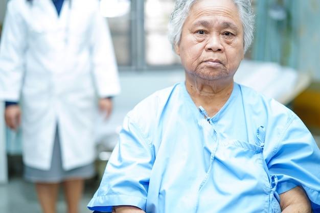 Behandeln sie hilfe und sorgfalt asiatischen älteren oder älteren frauenpatient der alten dame, der auf rollstuhl sitzt.