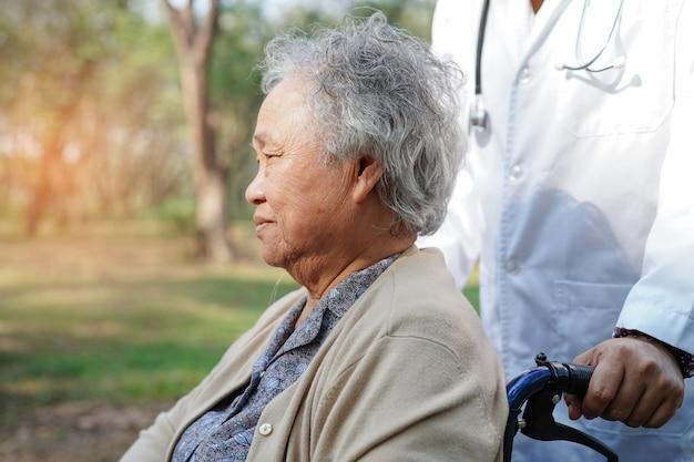 Behandeln sie hilfe und sorgfalt asiatischen älteren oder älteren frauenpatienten alter dame, der auf rollstuhl sitzt