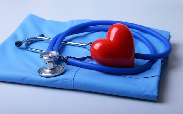 Behandeln sie mantel mit medizinischem stethoskop und rotem herzen auf dem schreibtisch