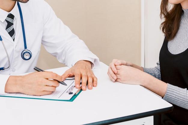 Behandeln sie medizinische kontrolluntersuchungsinformationen mit frauenpatienten auf doktortabelle im krankenhaus gesundheitswesen und medizin