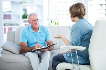 Behandeln Sie Schreiben in Buch beim Sitzen durch Patienten zu Hause