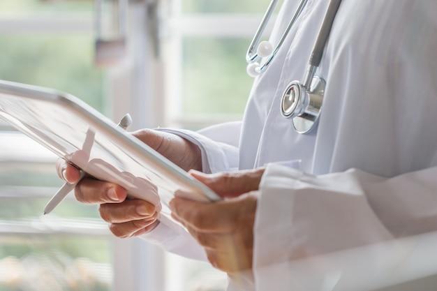 Behandeln sie stellung unter verwendung des tablet-computers mit weißer kleiderreihe und tragendem stethoskop auf hals
