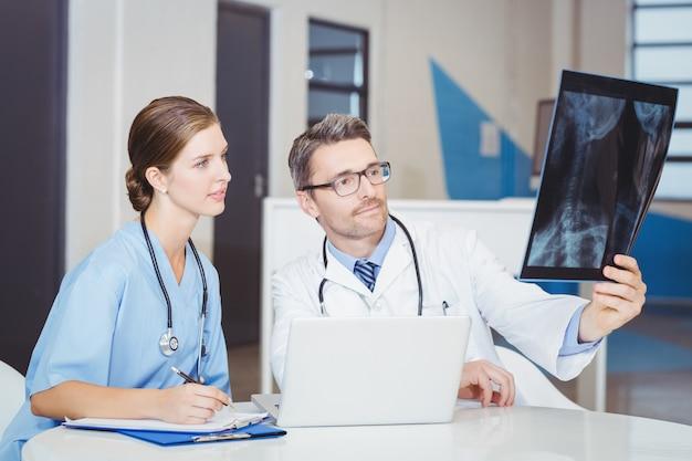 Behandeln sie untersuchungsröntgenstrahl mit dem kollegen, der am schreibtisch sitzt