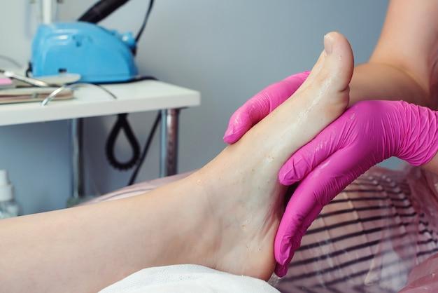 Behandlung der füße. schönheitsbehandlung für die beine. pediküremeister massiert die füße mit peeling. professionelle pediküre im schönheitssalon. frau, die sich im salon entspannt und sich um die nägel kümmert.