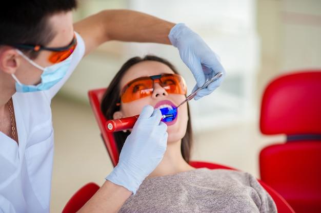 Behandlung des schönen mädchens der lichtdichtung in der zahnmedizin.