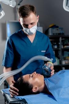 Behandlung einer schweren form des coronovirus covid-19. der arzt setzt auf der intensivstation eine maske zur künstlichen beatmung der lunge auf
